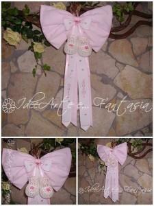 Idea per un fiocco nascita, decorato con scarpine all'uncinetto e ricamo a punto croce