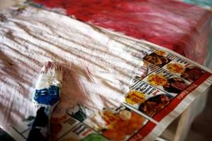 Dipingere con dell'acricilico rosa e bianco, ddella vecchia carta da giornale